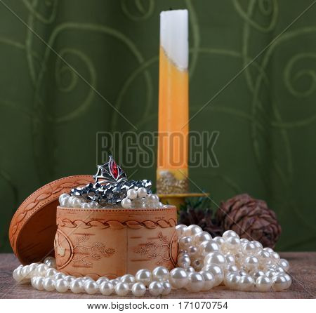 small birch bark casket with jewelry surrounded by pearls on unfocused background of candle and cones