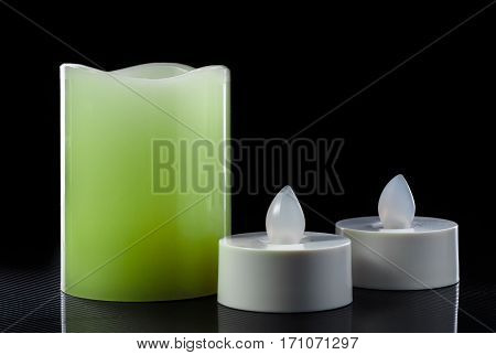 colored led candles on glossy surface on black background