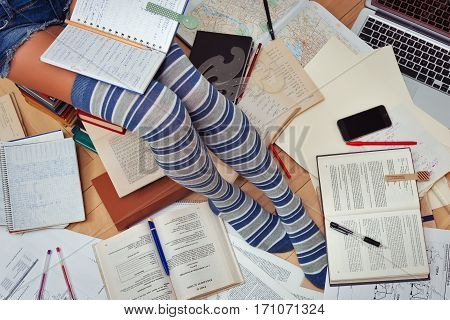 Teenage girl in tabby half-hoses and jeans shorts studying hard with her textbooks, copybooks and so on