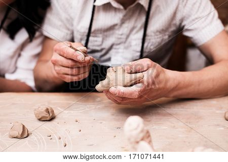 hands holding a clay in a clay studio