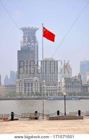 National Flag of China, with the Bund skyline in the background, City of Shanghai, China.