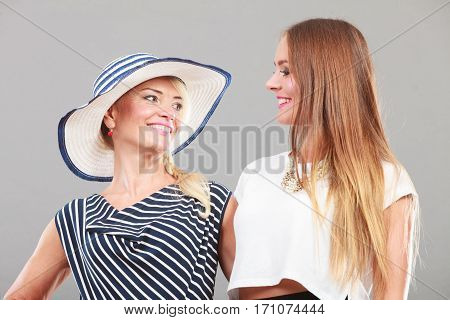 Fashionable style clothes concept. Woman wearing white top standing next to older female with striped dress