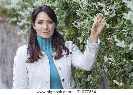 Beautiful lady next to a flowering plant. People