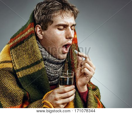 Ill Man covered with plaid blanket take medicine pill with a glass of water . Sick man suffering cold and winter flu virus. Health care concept