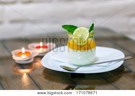 milk dessert with lime at the table by candlelight