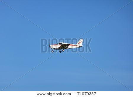 Photo of a small red and white airplane flying in the sky