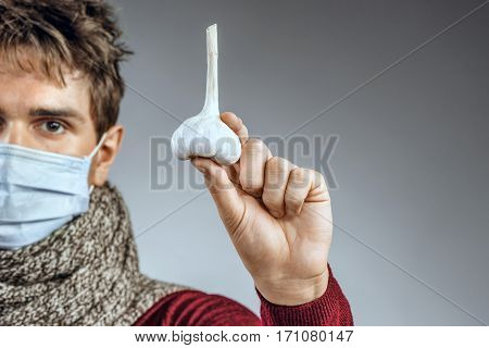 Ill man holding garlic. Photo of man wears protective mask against infectious diseases and flu. Close up. Healthcare concept
