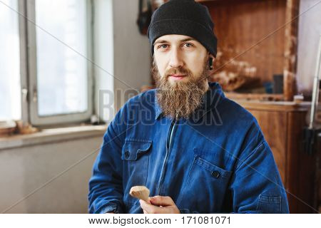 Worker with a beard wearing blue jeans suit and black hat holding a wooden spoon and looking at camera, woodcarving, portrait, copy space.