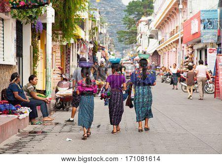 PANAJACHEL, GUATEMALA-DEC 24, 2015: : Tree guatamalian young girls salling traditional  colorful fabric at the street market  in Panajachel, on Dec 24, 2015, Guatemala.