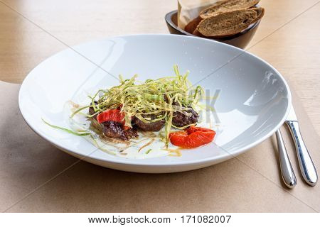 Beef medallions with greens, fry, red boiled pepper and white cheese sauce on a white plate, brown bread, restaurant table