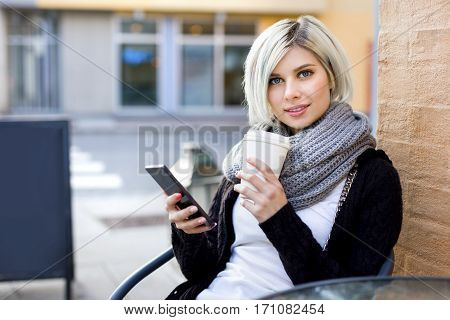 Portrait of beautiful young woman with mobile phone and disposable coffee cup at sidewalk cafe