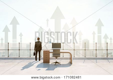 Back view of businessman in abstract roof office with bright daylight and abstract upward arrows. Success concept