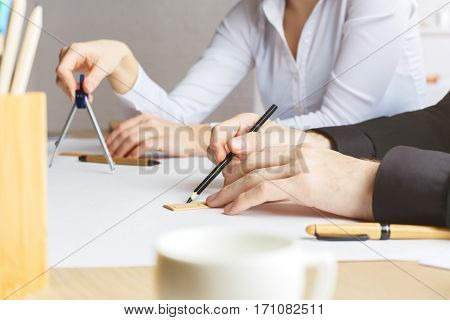 Side view of male and female hands drawing blueprints using rulers compasses and pencils. Young engineers at workplace