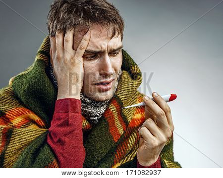 Shocked man reading his temperature on thermometer. Photo of sick man suffering cold and winter flu virus.