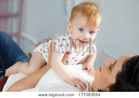 Funny kid with red hair and blue eyes,dressed in a white t-shirt with grey stars and plays on the bed in the bedroom with his mother,a woman with black hair,dressed in a white t-shirt and blue jeans,the woman's nails painted red nail Polish