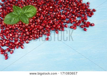 Background made of red pomegranate seeds. The scattered red grains of a pomegranate with copy space for text. Top view.