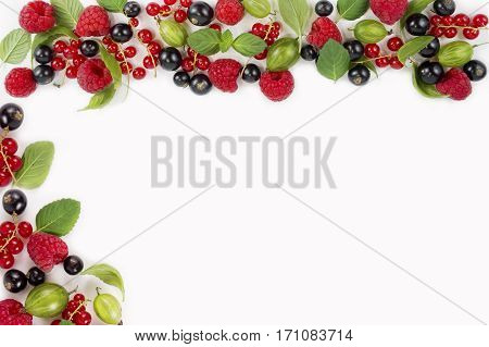 Various fresh summer berries on white background. Ripe raspberries currants gooseberries mint and basil leaves. Berries at border of image with copy space for text. Background berries.