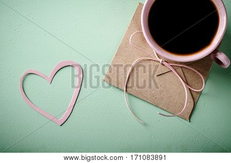 Love letter, envelope with paper heart and pink cup of coffee. Valentines card. Horizontal, flat lay, top view