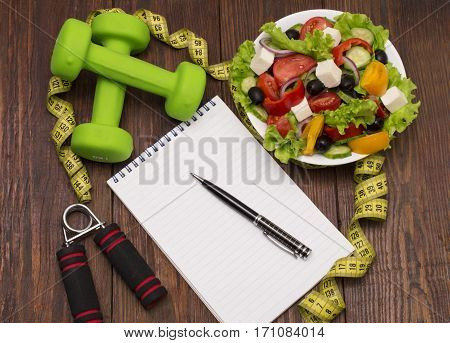 Workout and fitness dieting copy space diary. Dumbbell, vegetable salad and measuring tape on rustic wooden table.