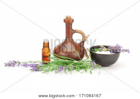 Lavender oil in a glass bottle essence in a clay jug and fresh flowers isolated on white background.