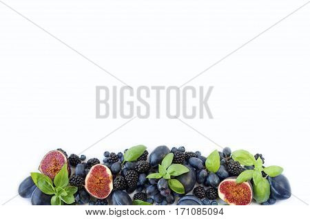 Blue and purple food. Group of fresh fruits and berries with basil's on a white background. Ripe blueberries blackberries grapes plums and figs. Top view with copy space.