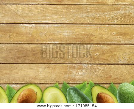 Fresh avocado with leaves on wooden background. Halves of fresh avocado at border of image with copy space for text. Top view. Vegetarian or healthy eating.