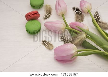 background with pink tulips and macaroons. Bouquet of tulips on white wooden table. Tulips with copy space for text.
