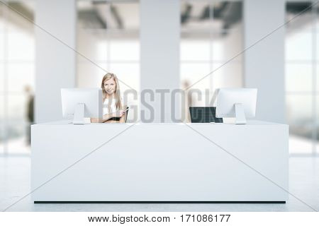 Attractive caucasian woman at white reception desk with computers in blurry concrete interior with daylight. Business concept. 3D Rendering