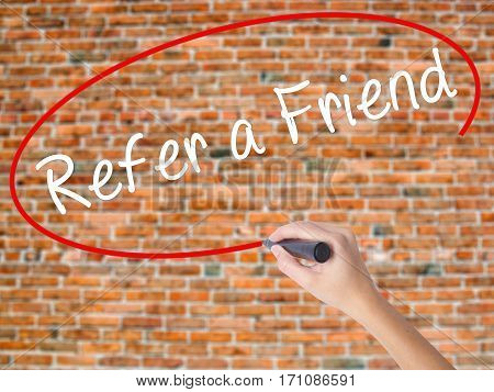 Woman Hand Writing Refer A Friend  With Black Marker On Visual Screen