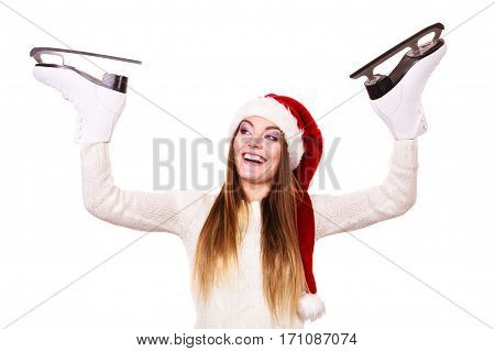 Winter sport activity. Young woman with ice skates getting ready for ice skating. Smiling cheerful girl wearing santa claus hat on white