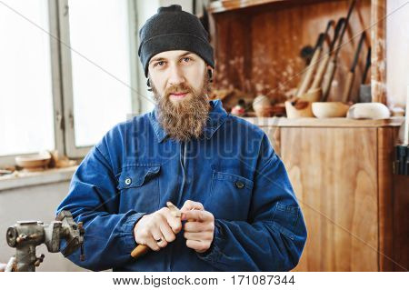 Worker with a beard wearing blue jeans suit and black hat carving wooden spoon with instruments and looking at camera, woodcarving instruments at background.