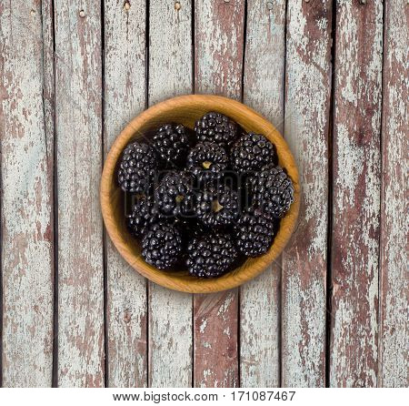 Blackberries in a wooden bowl. Top view. Ripe and tasty blackberries on a wooden background.