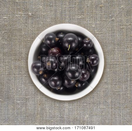 Black currants in a white ceramic bowl. Top view. Ripe and tasty currants on a linen tablecloth.