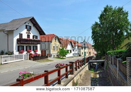 View of the residential houses and dry water canal in the alpine municipality Hohe Wand Stollhof. Lower Austria