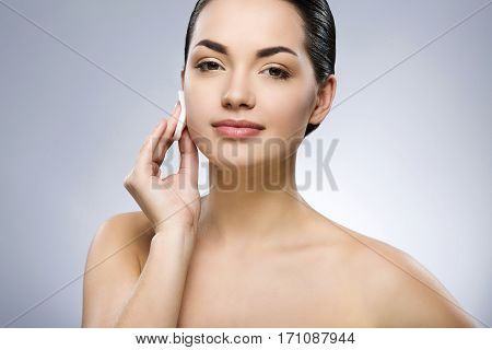 Cute girl with black fixed hair behind, big eyes and naked shoulders, looking at camera and cleaning face with cotton pad at gray studio background, close up.