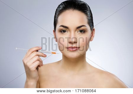 Lovely girl with black fixed hair behind, dark big eyes and naked shoulders looking at camera, holding syringe at gray studio background.