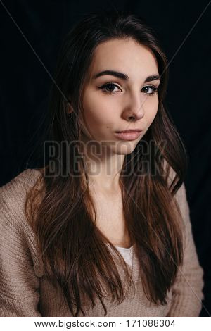 Beautiful brunette woman on black background. Close up of an attractive girl of European appearance.