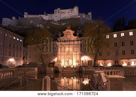 View of the Horse Well at the Kapitelplatz Square and Fortress Hohensalzburg on the mountain in night. Salzburg, Austria.