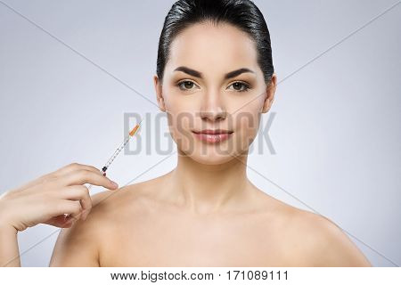 Lovely brunette girl with fixed hair behind, dark big eyes and naked shoulders looking at camera and holding syringe at gray background, portrait.