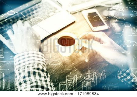 Businessman drinking coffee and using laptop at workplace with business charts. Filtered image