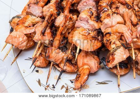 Seafood appetizers mix consisting of red salmon and tuna fish meat and shrimp on plate, close up