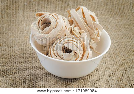 Rolled pasta in bowl on linen background. Ingredients for tasty dish.