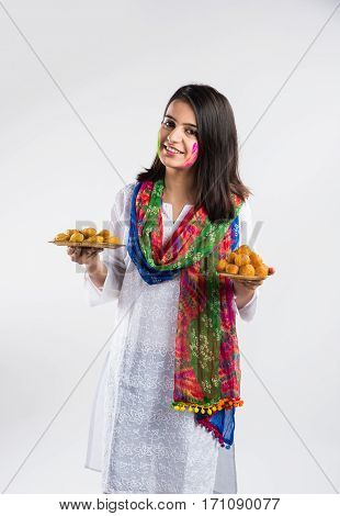indian pretty young girl holding a plate full of sweet bundi laddu or gujiya and powder colour called gulal or gulaal on indian festival called Holi, isolated over white background, selective focus