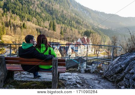 Couple sitting on bench near mountains