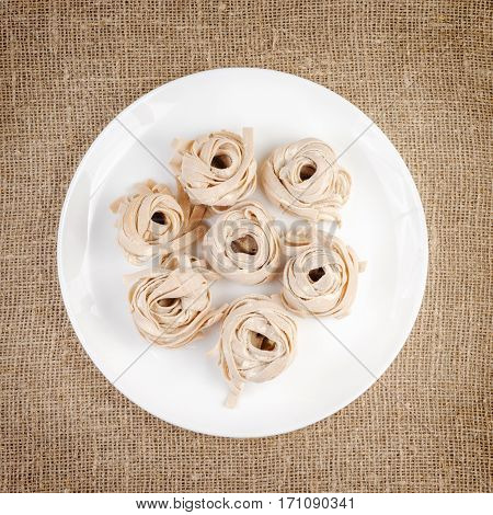 Homemade rolled pasta on linen background . Portion of raw fettuccine or tagliatelle or pappardelle. Dry pasta from whole wheat flour. Ingredients for tasty dish.