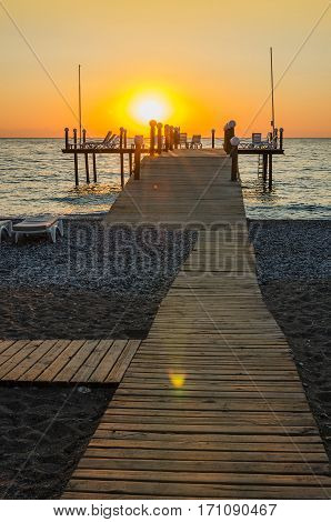 Wooden pier entering into the sea with colorful morning sky. Beautiful orange sunset over the ocean.