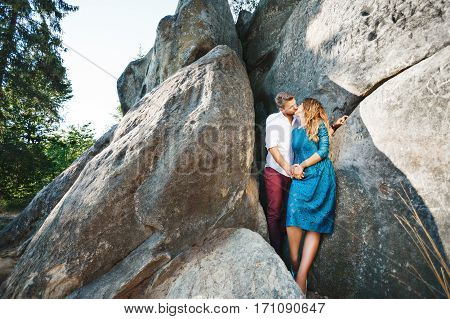 Cute couple standing together near rocks, outdoor. Beloved holding hands of each other and kissing. Girl wearing blue dress and man wearing white shirt and claret trousers. Full body