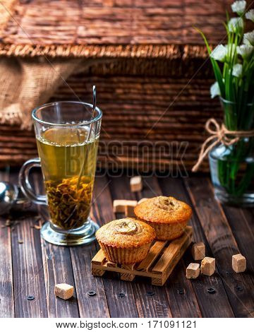 A couple of banana muffins on a wooden stand. Wooden background. Green tea in transparent Cup in the background. Selective focus