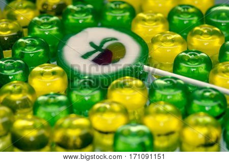 Colorful candy background with yellow and green sweetmeats. Apple lollipop. Holiday candy background. Dolce Vita.