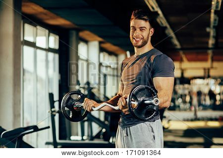 Handsome man doing biceps lifting in a gym